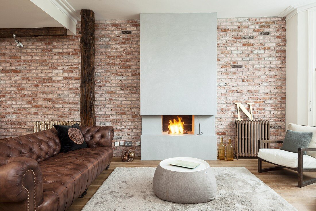 Lounge area with old leather sofa and coffee table on rug in front of modern fireplace in brick wall in open-plan interior