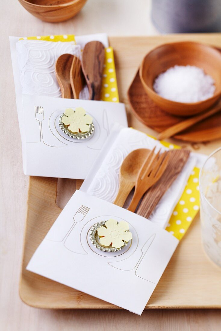 Wooden cutlery in lovingly made paper cutlery bags decorated with flattened bottle tops and flower motifs