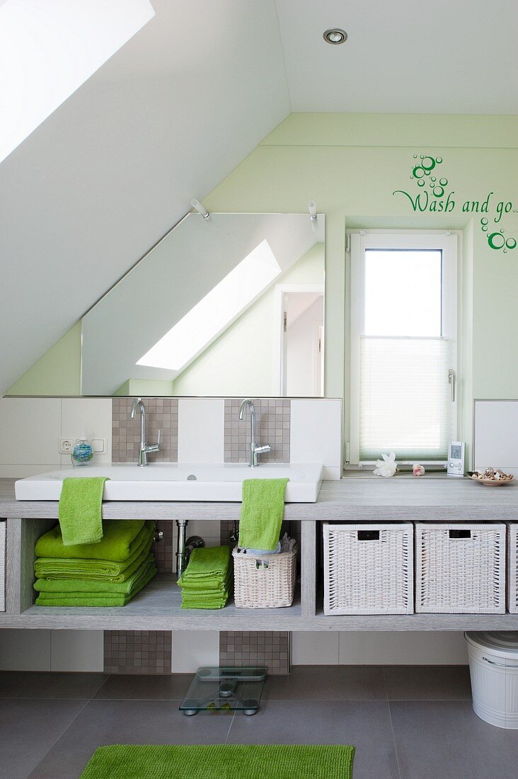 Children's attic bathroom - washstand on pale grey structure with storage, pastel green wall and message written next to narrow window