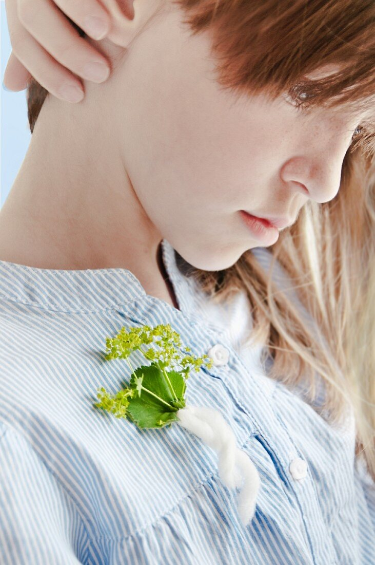 Girl with sprig of lady's mantle pinned to dress