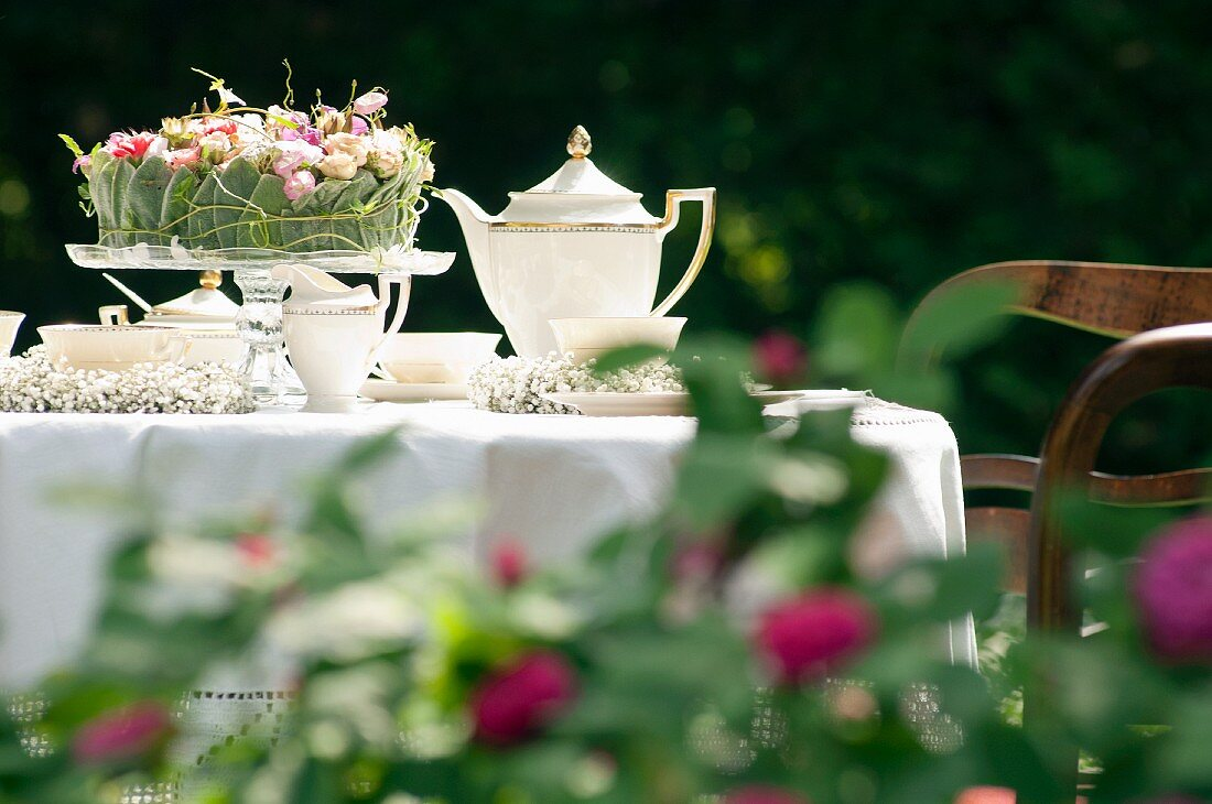 Romantically set coffee table in garden with white tablecloth and flower arrangement on glass cake stand