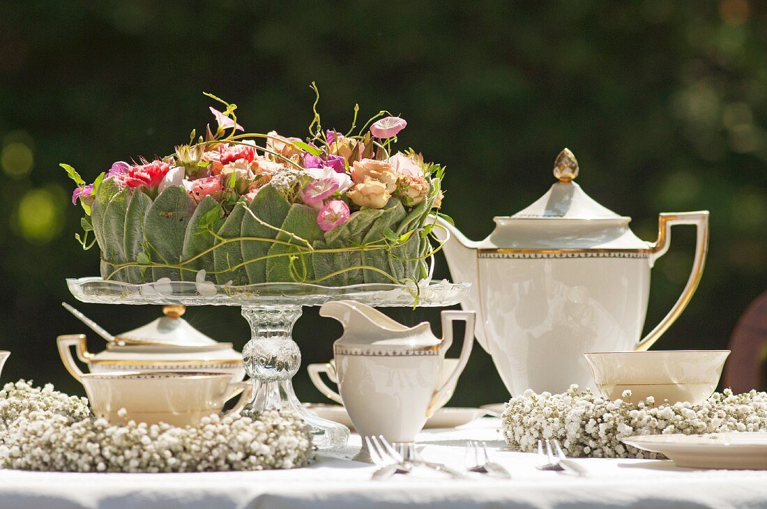 Elegant, romantic coffee table in garden set with flower arrangement on glass cake stand and delicate wreaths of gypsophila
