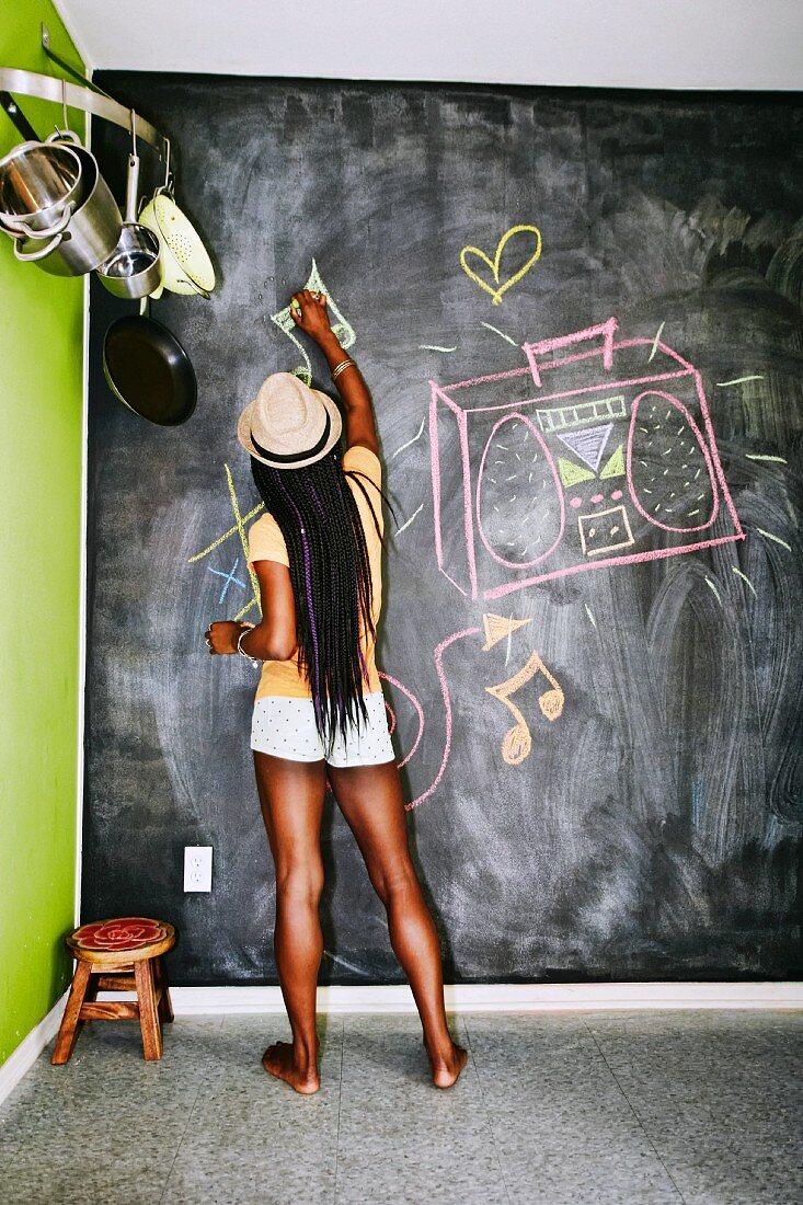 Woman drawing on blackboard wall