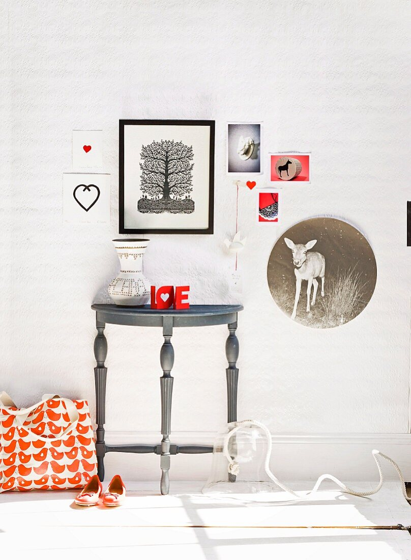 Wall lovingly decorated with pictures above console table