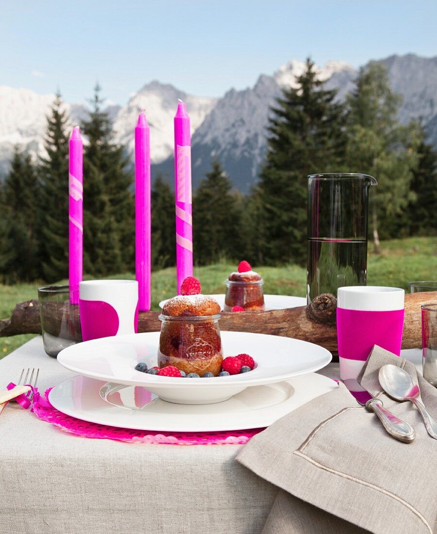 Dessertteller und pinkfarbene Kerzen auf festlich gedecktem Tisch, im Hintergrund Alpenblick