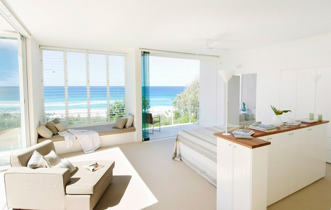 Half-height cabinet in front of bed and armchair next to panoramic window with sea view in spacious, white, light-flooded bedroom