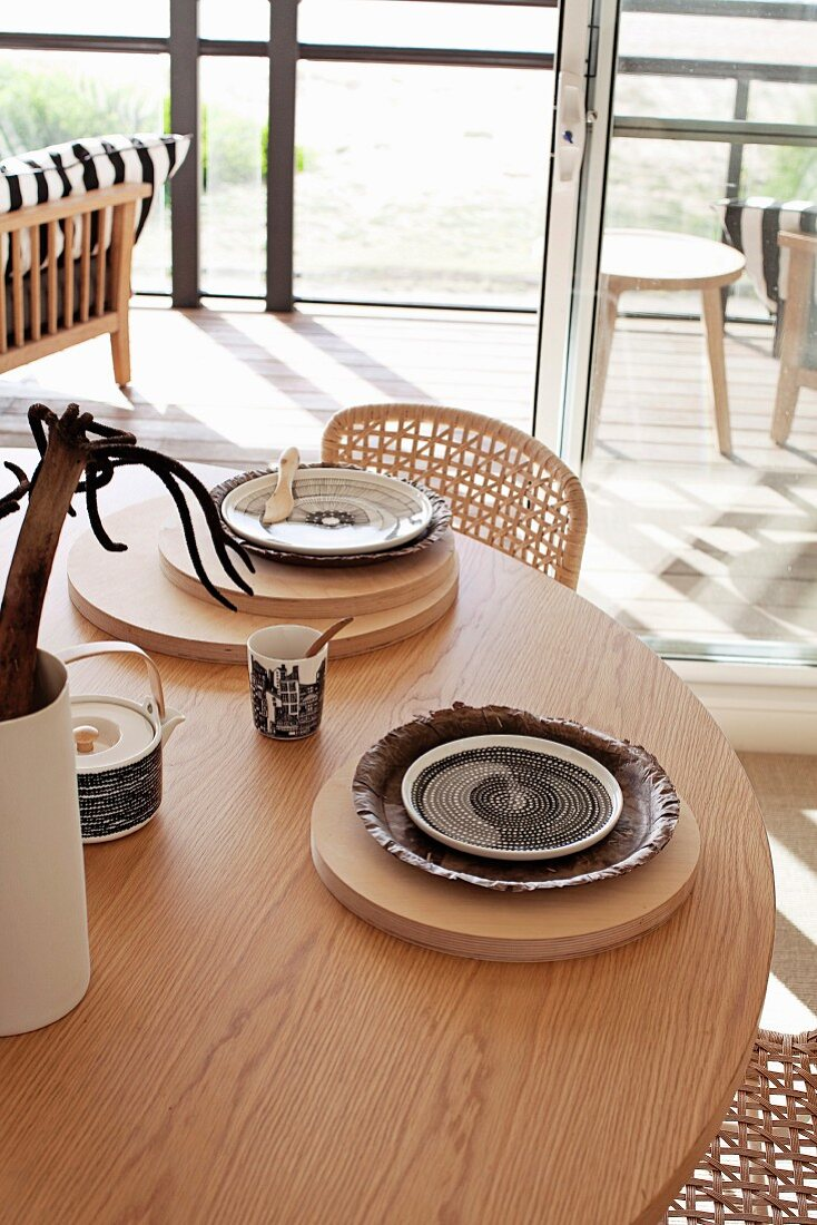Place settings on wooden boards on round wooden table