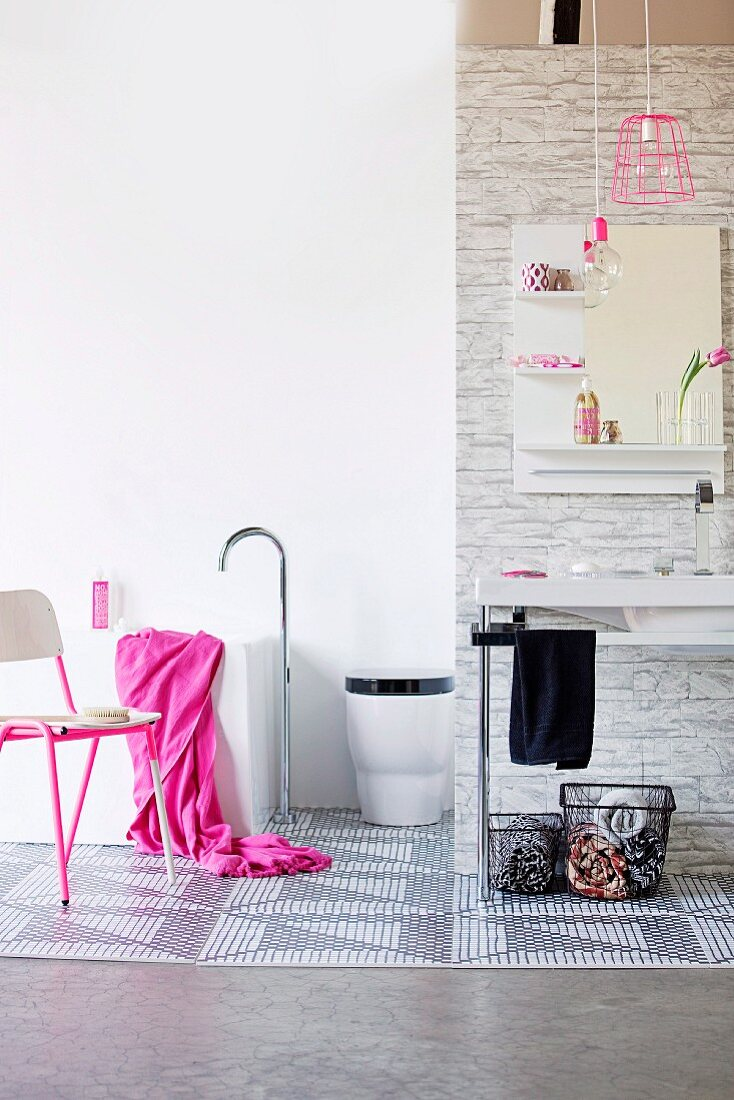Baskets below minimalist washstand, chair with pink metal frame and bright pink towel on bathtub with floor-mounted tap fittings in bathroom