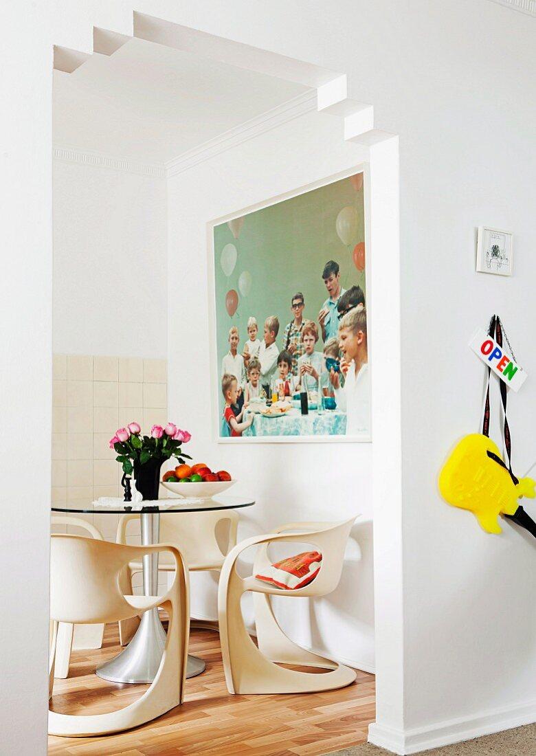 Blick durch Durchgang auf Essplatz mit weissen Schalenstühlen und rundem Glastisch vor Wand mit grossformatigem Foto