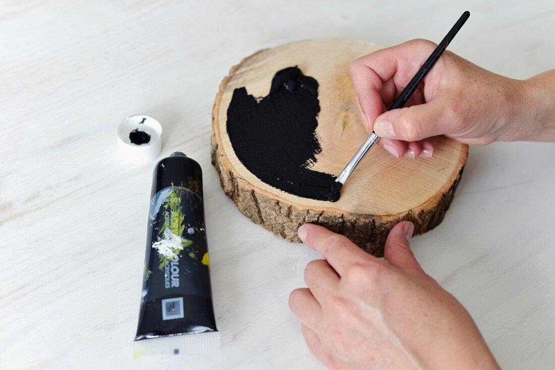 Bemalen einer Holzscheibe mit Pinsel und schwarzer Farbe