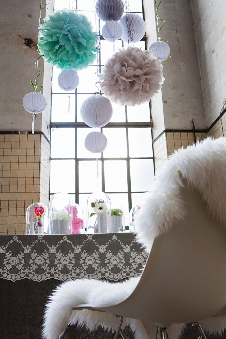 Feminine, romantic party decorations; pompoms, nostalgic lace tablecloth and flower arrangements on dining table in high-ceilinged, disused factory with industrial windows