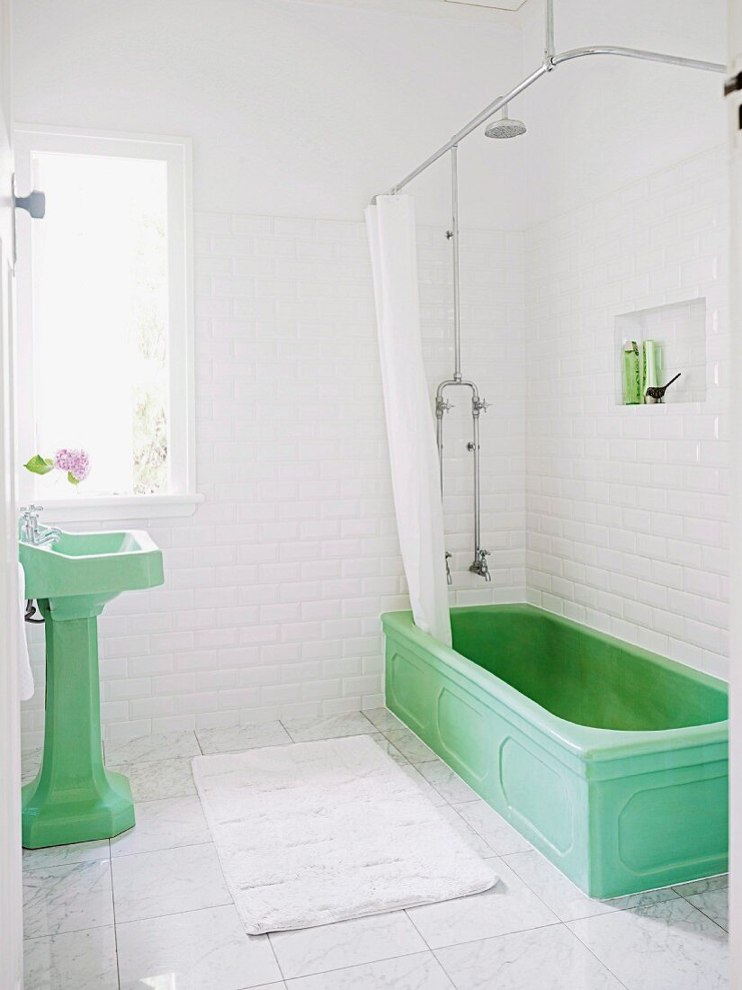 Green vintage pedestal sink and vintage bathtub with shower curtain in white-tiles bathroom with marble floor