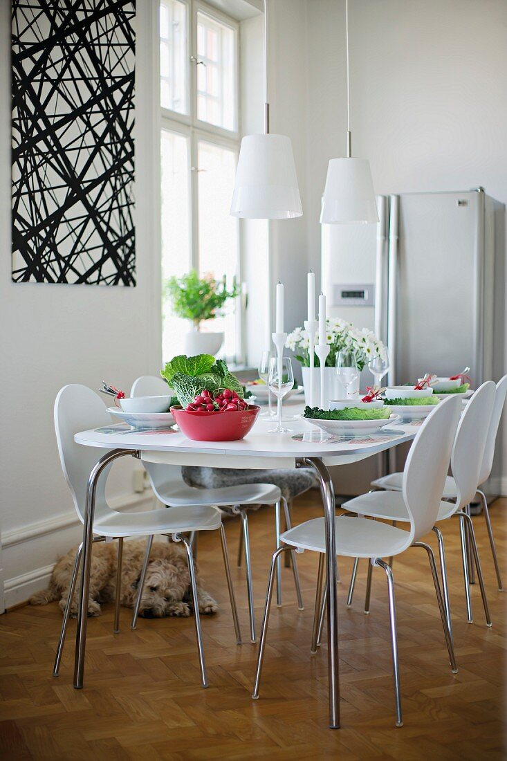 Dining room with white shell chairs and matching dining table with retro-style metal frame in traditional interior with modern ambiance