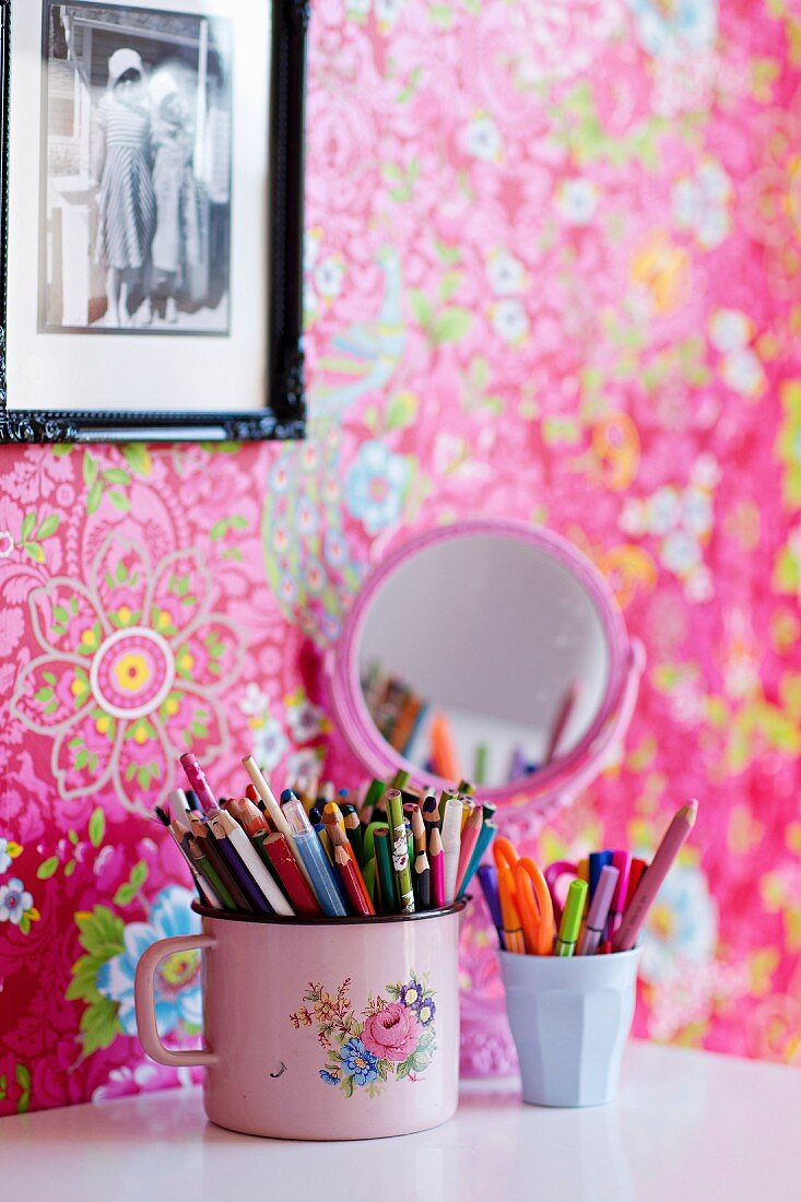 Beakers of pens on white surface, framed photo on pink wallpaper with floral pattern