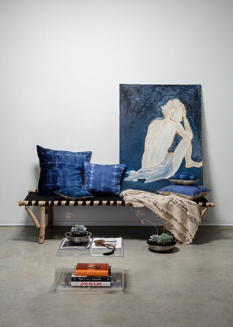Hand-dyed indigo cushions and nude painting of woman on bamboo couch with fabric seat behind plexiglas side table