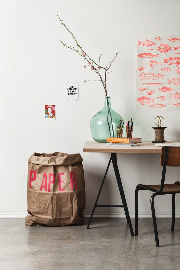 Large paper rubbish sack printed with red letters next to writing utensils and flowering branches in demijohn on desk