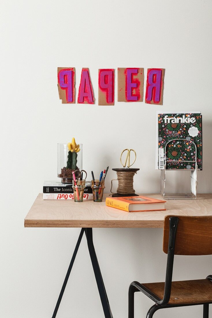 Detail of desk with office supplies below printed paper templates on wall