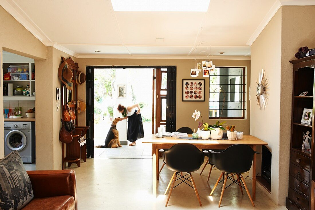 Dining area with classic chairs and living area with leather sofa in open-plan house; cloakroom with wide, open front door and woman and dog outside