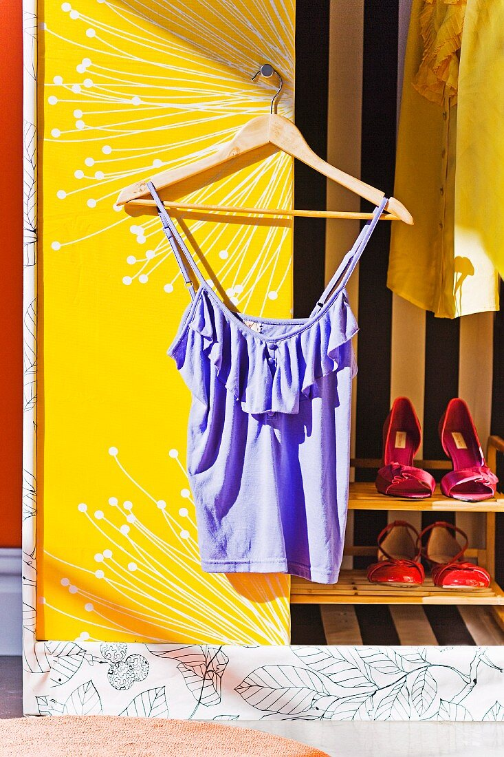 Top hanging on coathanger against white and yellow panel of wardrobe door and shoes on shelves