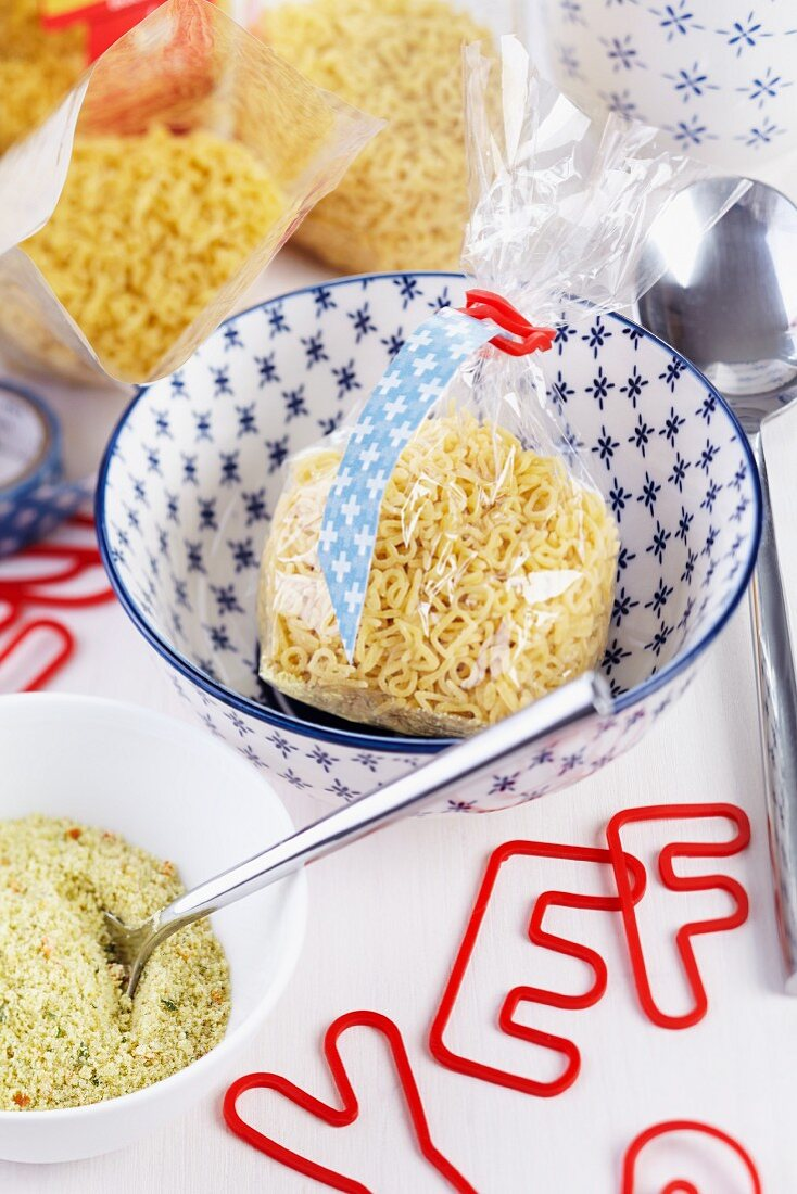 Packets of alphabet noodles in small bowls and red, alphabet-shaped elastic bands