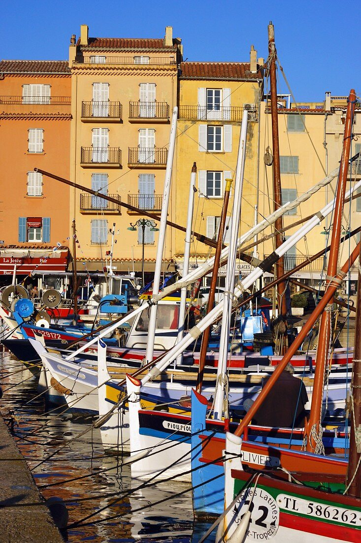 Boots in front of yellow-painted houses in Saint-Tropez harbour