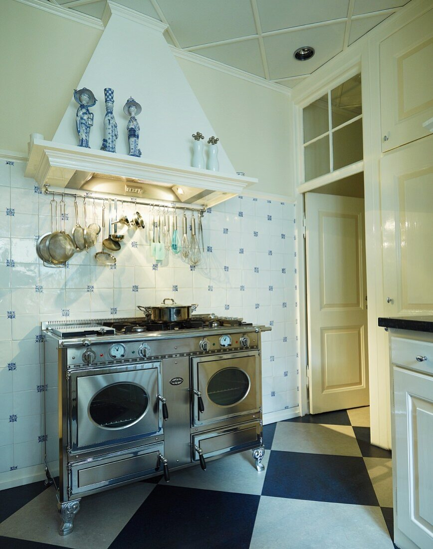 Vintage, stainless steel cooker under kitchen utensils suspended from extractor hood on tiled wall and diagonal chequered floor