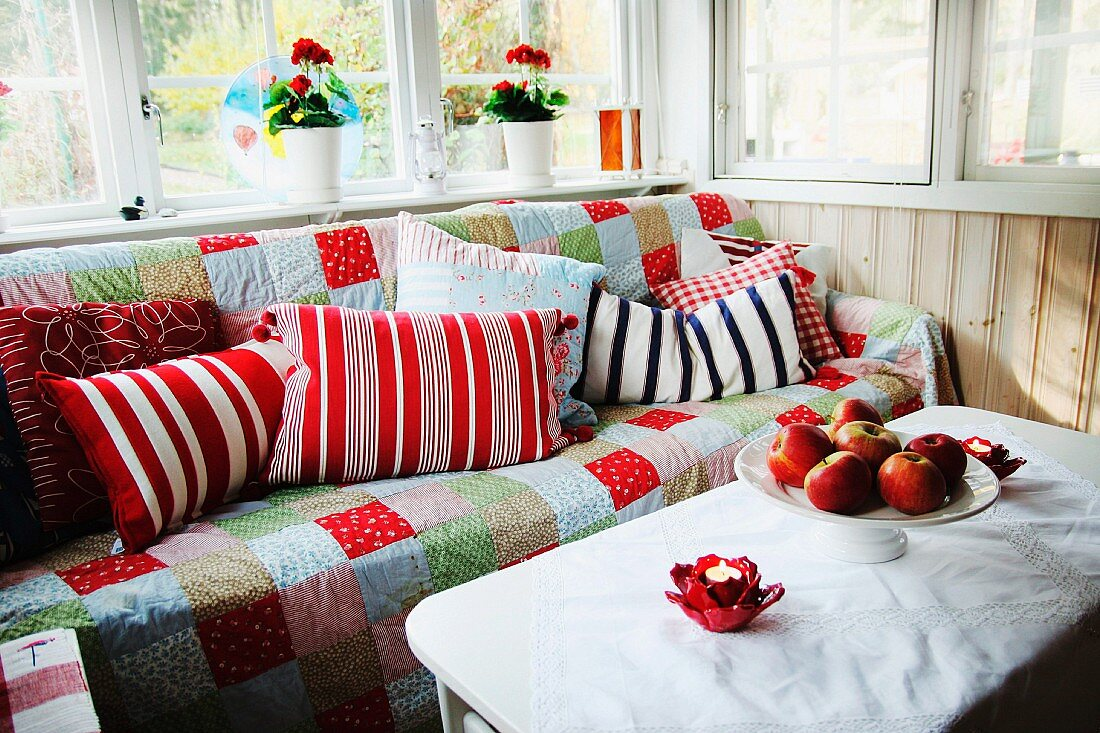 Comfortable corner in loggia - bowl of apples on white table in front of sofa with patchwork throw and patterned scatter cushions