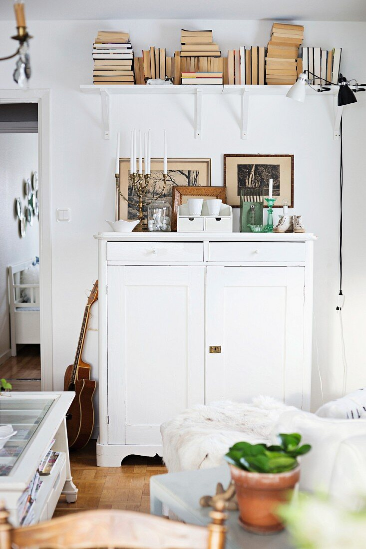Half-height, white wooden cabinet and books on wall-mounted shelf in rustic living room