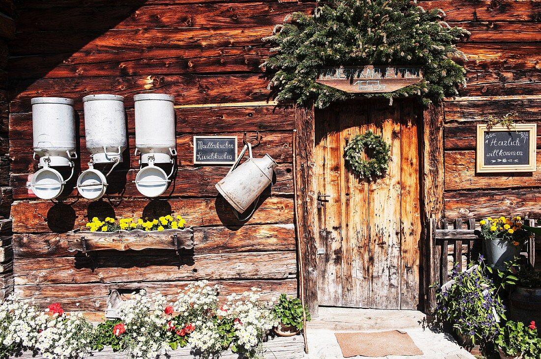 Alpine cabin with milk churns and decorative flower pots (Austria)
