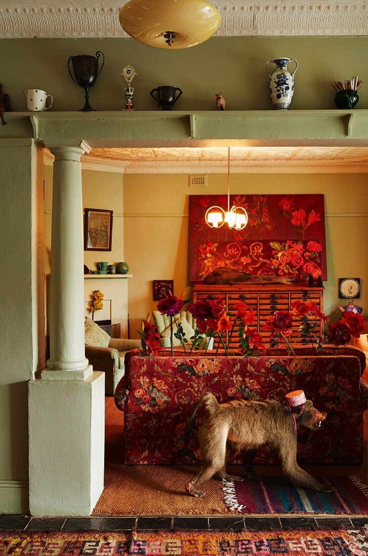 View through wide, open doorway with pillar; stuffed monkey against back of sofa with vintage floral pattern in artistic interior