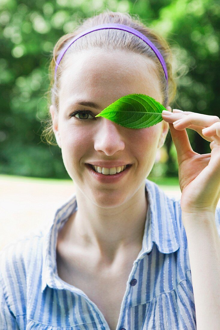 A young woman covering her eye with a leaf