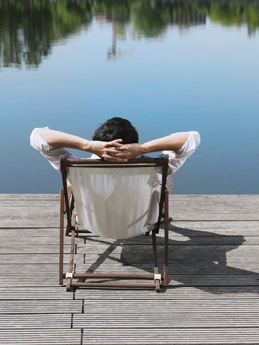 Rear view of a man sitting in a deck chair on a jetty