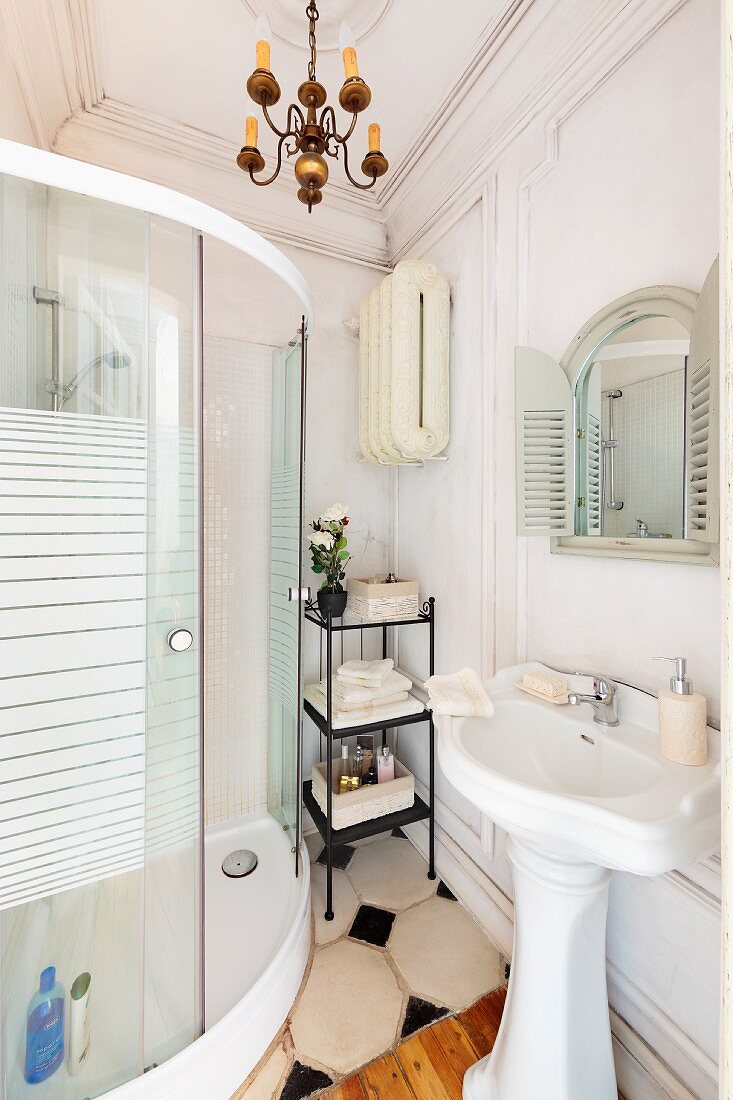 Vintage pedestal sink opposite modern, curved, glass shower cabinet in traditional bathroom with wood-clad wall and stucco frieze on ceiling