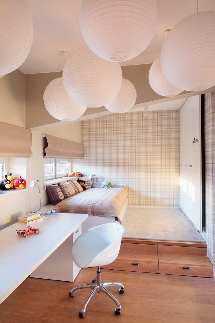 Multiple spherical pendant lamps made of white paper above swivel chair with white shell seat and desk; bed on platform in background in sleeping area with pale tartan wallpaper