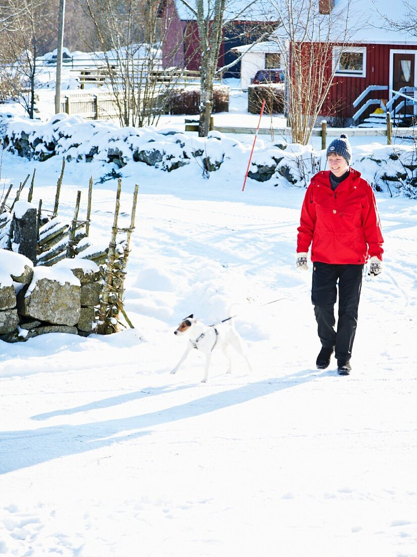Woman and dog on snowy street in Scandinavia