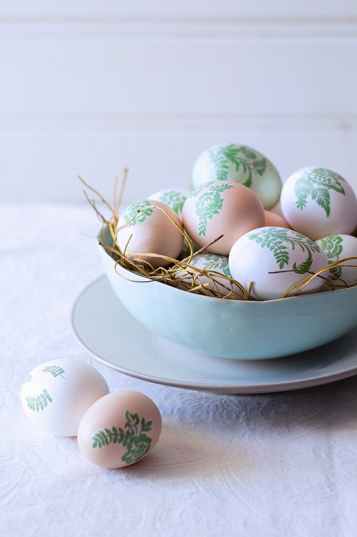 Easter eggs decorated with botanical patterns (decoupage) in nest of straw in bowl