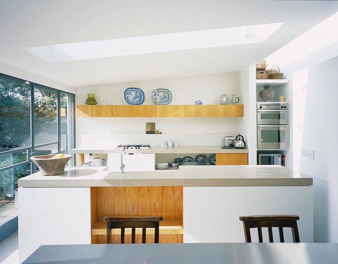 White designer kitchen with kitchen unit under a skylight in contemporary architecture