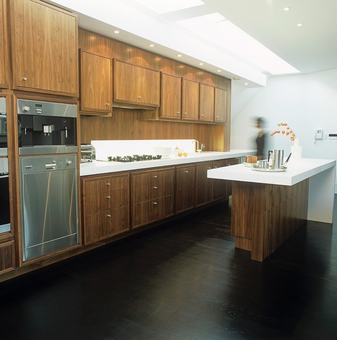 An open-plan, fitted kitchen with wooden cupboards and a bar with a white surface