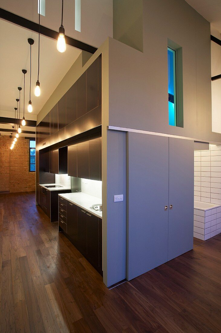 Kitchen, bathroom and stairwell window illuminated in coloured light in central, compact unit in a London loft apartment