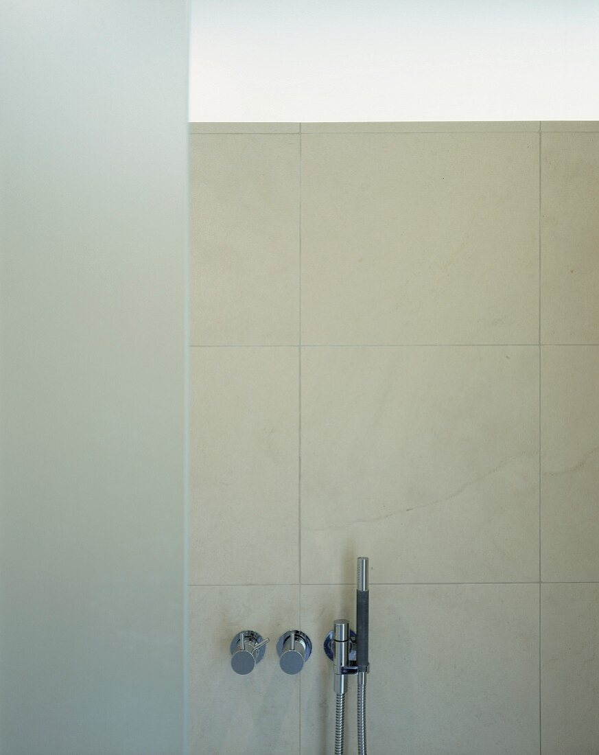 Contemporary hand shower on wall with tiles in natural shades