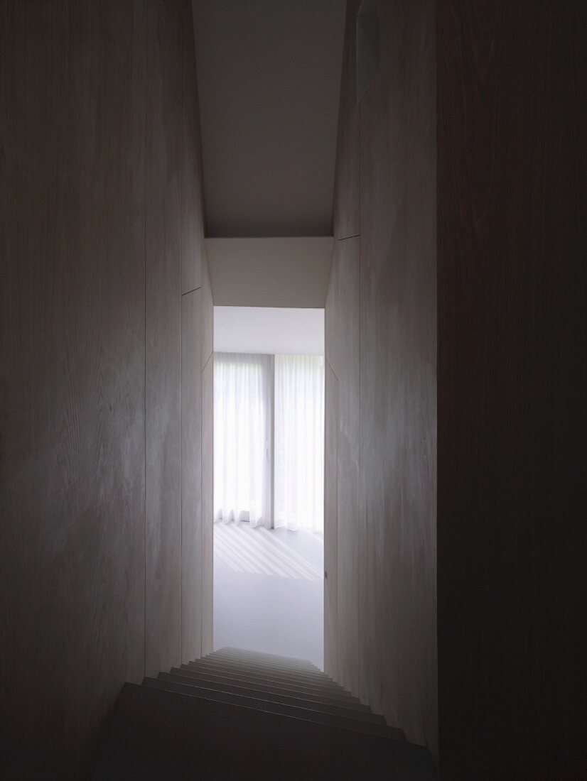 Narrow, high stairwell without handrail and view of sunny room with vertical blinds
