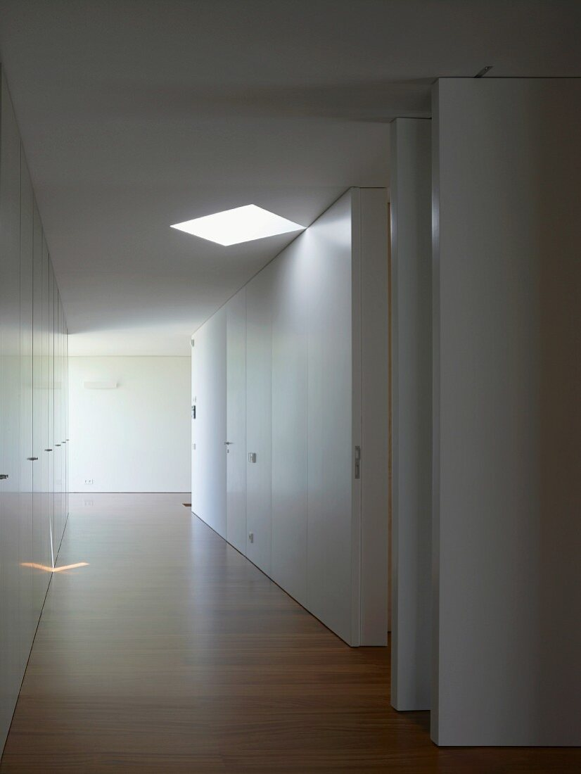 Hallway with floor-to-ceiling, white fitted cupboards