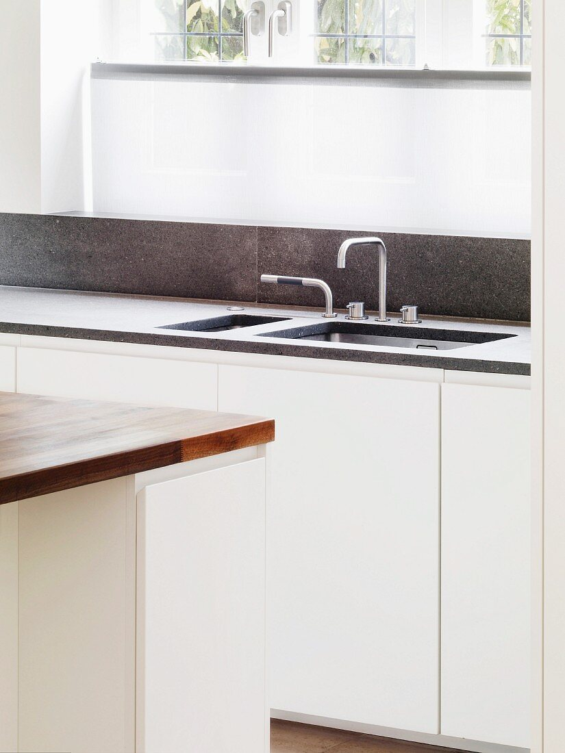 Kitchen unit with sink and designer fittings in front of window