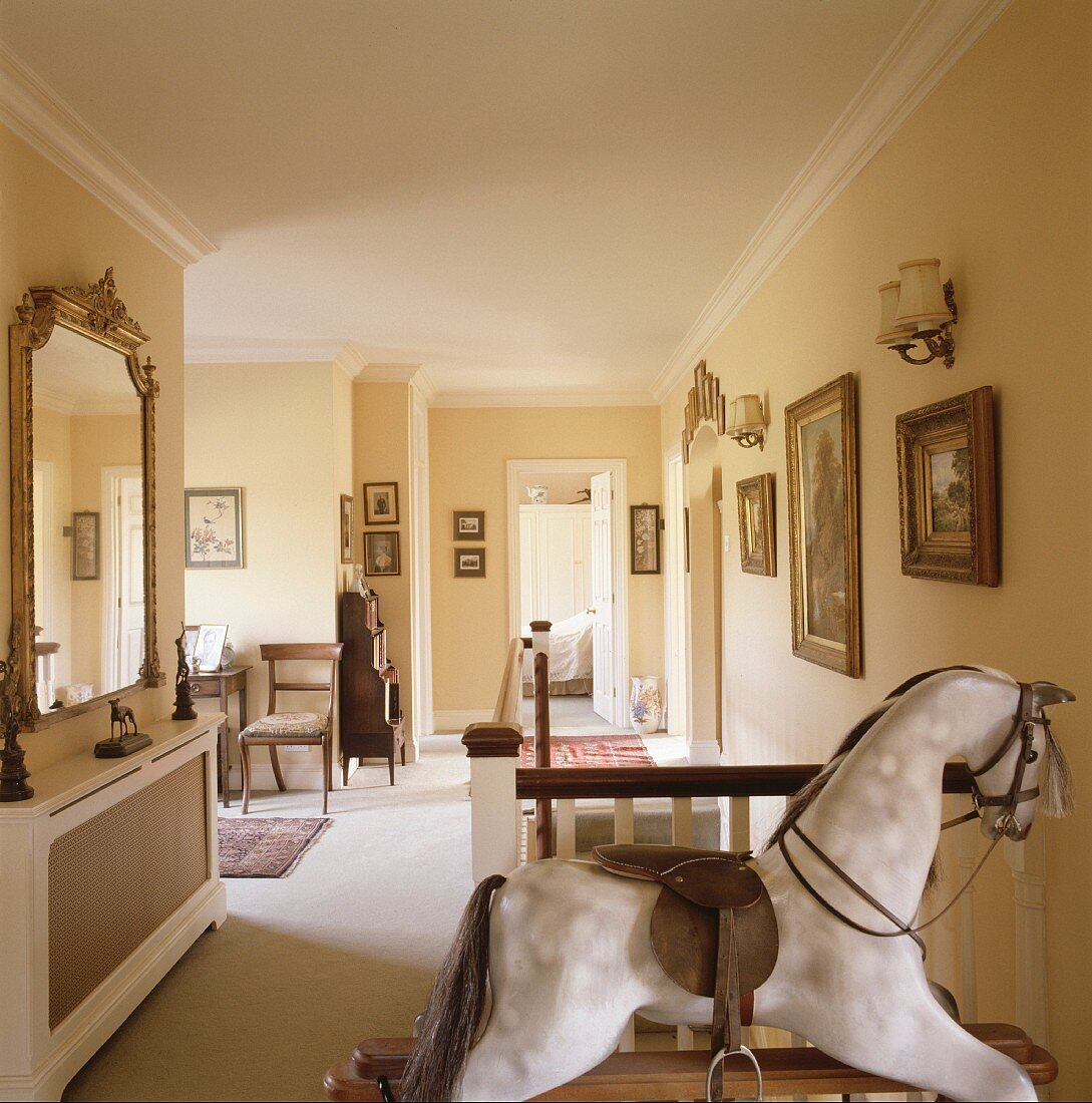 Antique rocking horse and gilt-framed pictured on traditional landing