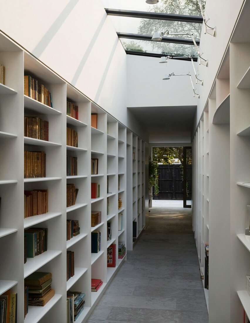 Library corridor with slanting skylight and glass door leading to courtyard