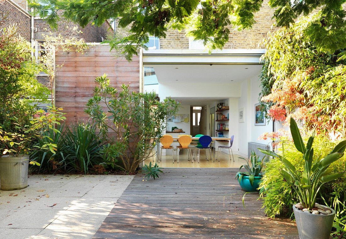 Wooden terrace with flower bed in front of house and view into open-plan dining room