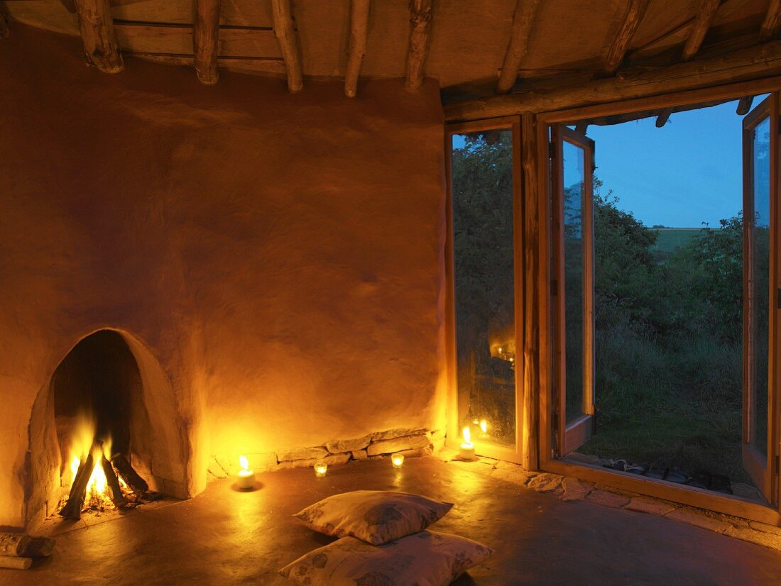 Burning open fire, candlelight and floor cushions in front of open terrace door in simple clay house