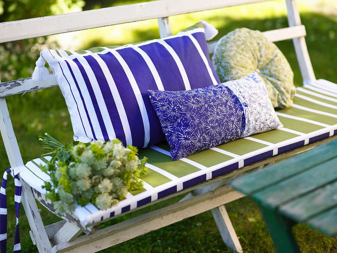 White lacquered garden bench with colorful pillows and seat cushion