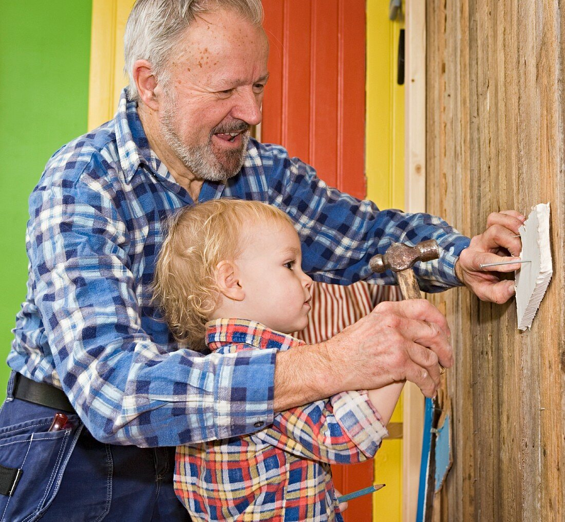 Grandfather and grandson hammering a nail into a wall