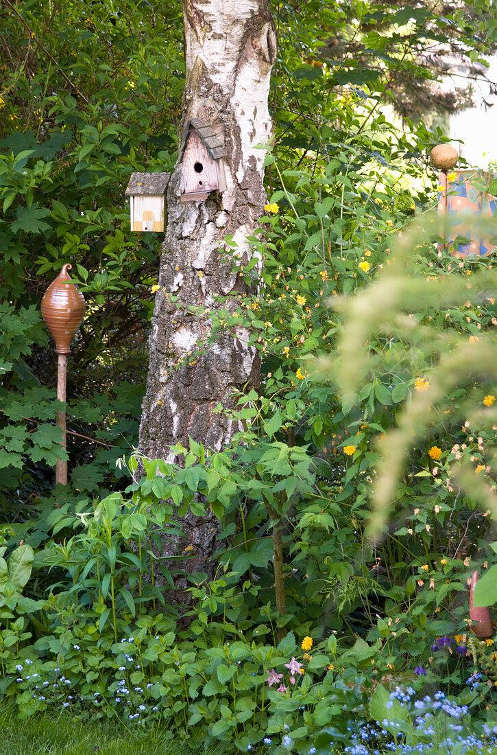Bird box on tree trunk next to ceramic ornament